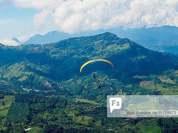 Paraglider soars near Jardin  Antioquia  Colombia  South America