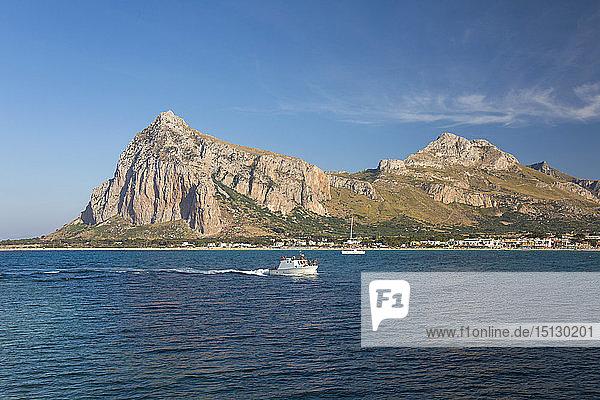 View across the bay to Monte Monaco and Pizzo di Sella  small boat returning to port  San Vito Lo Capo  Trapani  Sicily  Italy  Mediterranean  Europe