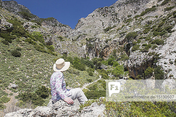 Hiker on rocks admiring view into the Rouvas Gorge  Zaros  Iraklio (Heraklion)  Crete  Greek Islands  Greece  Europe