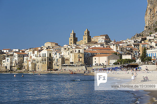 View from beach along water's edge to the town and UNESCO World Heritage Site listed Arab-Norman cathedral  Cefalu  Palermo  Sicily  Italy  Mediterranean  Europe