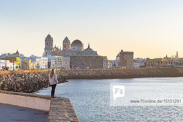 Woman enjoying the view of Santa Cruz Cathedral and ocean seen from the promenade along quayside  Cadiz  Andalusia  Spain  Europe
