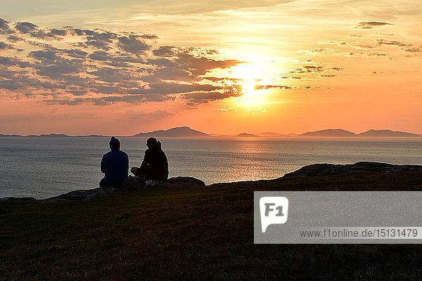 Two tourists enjoying a beautiful sunset at Neist Point on the Isle of Skye  Inner Hebrides  Scotland  United Kingdom  Europe