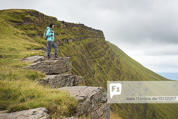A woman looks out from a high escarpment while hiking in the Brecon Beacons National Park mountain range  Wales  United Kingdom  Europe