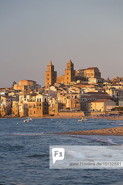 View from beach along water's edge to the town and UNESCO World Heritage Site listed Arab-Norman cathedral  sunset  Cefalu  Palermo  Sicily  Italy  Mediterranean  Europe