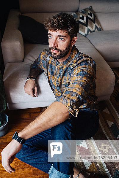 Mittelgroßer erwachsener Mann sitzt auf dem Wohnzimmerboden und starrt