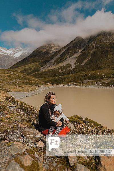 Mutter mit Baby genießt malerische Aussicht am See  Wanaka  Taranaki  Neuseeland