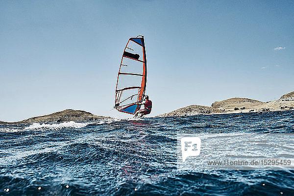 Zurückgelehnter junger Mann beim Windsurfen auf Meereswellen  Seitenansicht  Limnos  Khios  Griechenland Zurückgelehnter junger Mann beim Windsurfen auf Meereswellen, Seitenansicht, Limnos, Khios, Griechenland