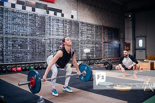 Young man watching woman lift barbell in gym