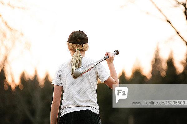 Mädchen mit Baseballschläger über der Schulter auf dem Lande  Rückansicht