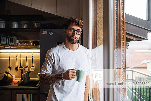 Mid adult man with coffee by apartment window  portrait
