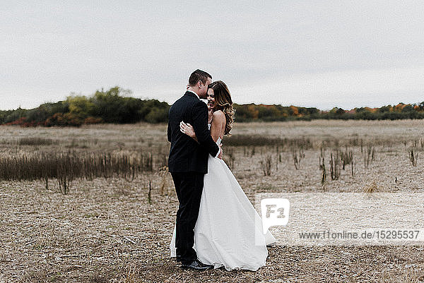 Romantische junge Braut und Bräutigam im Feld umarmend  in voller Länge