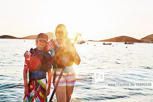 Mutter und Sohn stehendes Paddelbootfahren auf See  Portrait  Limnos  Khios  Griechenland Mutter und Sohn stehendes Paddelbootfahren auf See, Portrait, Limnos, Khios, Griechenland