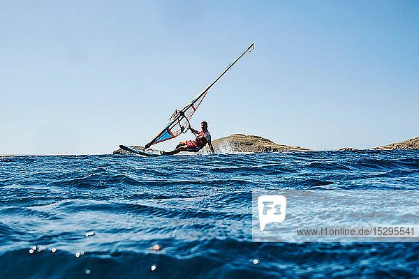 Zurückgelehnter junger Mann beim Windsurfen auf Meereswellen  Blick auf die Oberfläche  Limnos  Khios  Griechenland Zurückgelehnter junger Mann beim Windsurfen auf Meereswellen, Blick auf die Oberfläche, Limnos, Khios, Griechenland