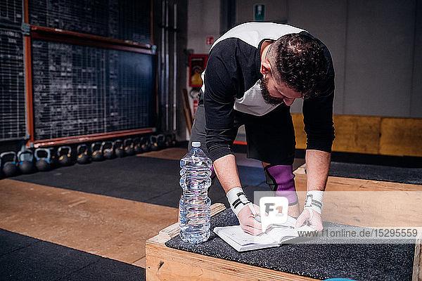 Junger Mann liest Checkliste am Notebook im Fitnessstudio