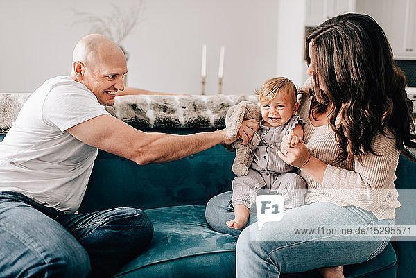 Mutter und Vater auf dem Sofa  während die kleine Tochter mit einem Plüschtier spielt
