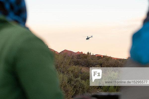 Zwei Personen beobachten Hubschrauber über der Berglandschaft  über die Schulter gesehen  Kapstadt  Westkap  Südafrika