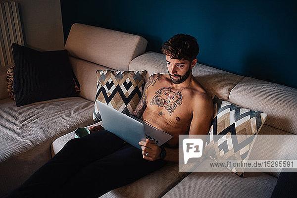 Mittelgroßer erwachsener Mann mit tätowierter Brust auf dem Sofa beim Blick auf den Laptop