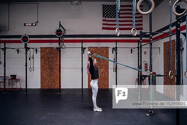 Junge Frau  die im Fitnessstudio die Arme streckt