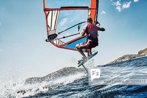 Junger Mann in der Luft beim Windsurfen auf Meereswellen  Seitenansicht  Limnos  Khios  Griechenland Junger Mann in der Luft beim Windsurfen auf Meereswellen, Seitenansicht, Limnos, Khios, Griechenland