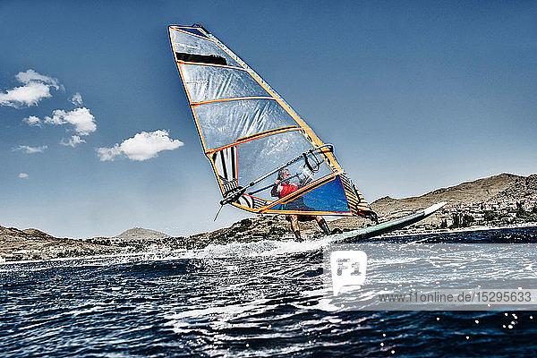 Junger Mann lehnt sich beim Windsurfen auf Meereswellen zurück  Limnos  Khios  Griechenland Junger Mann lehnt sich beim Windsurfen auf Meereswellen zurück, Limnos, Khios, Griechenland