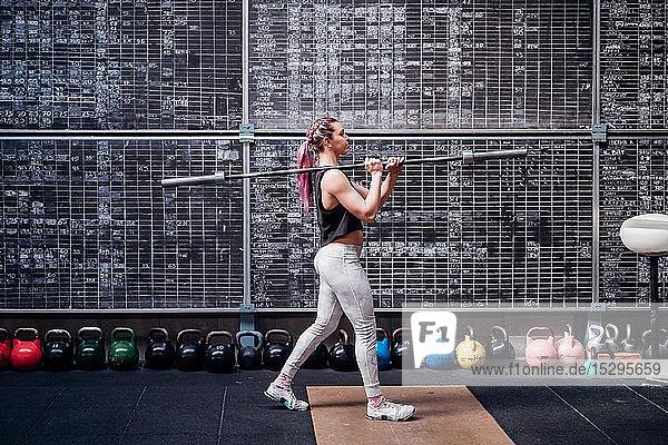 Junge Frau hebt Hantel im Fitnessstudio