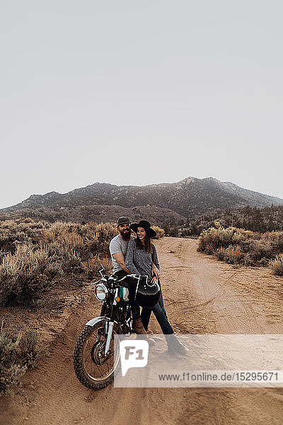 Couple relaxing on motorbike  Kennedy Meadows  California  US
