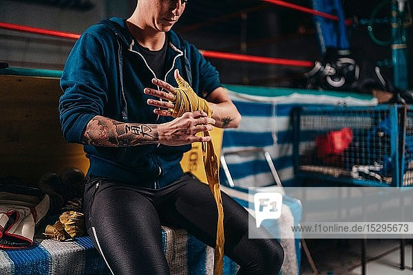Boxer putting on handwrap in gym