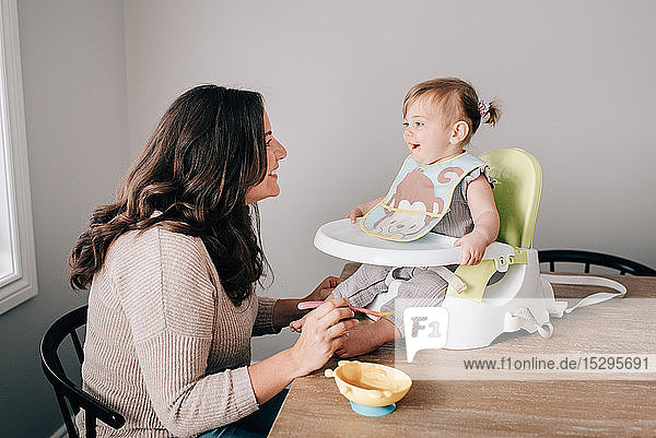 Mother feeding baby daughter in child seat on kitchen table