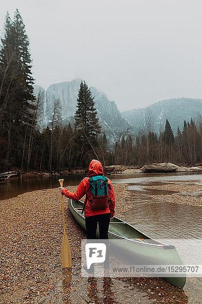 Junge Kanutin bei der Vorbereitung eines Kanus im Fluss  Rückansicht  Yosemite Village  Kalifornien  USA
