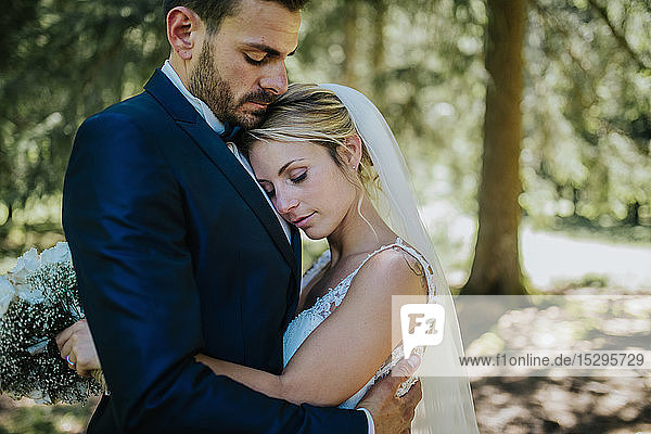 Romantic bride and groom hugging each other in woodland