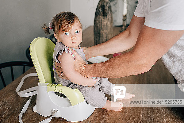 Father putting baby daughter in child seat  cropped portrait