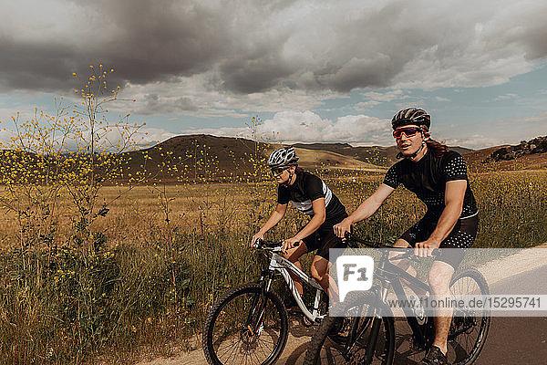 Junges Radfahrerpaar radelt auf einer Landstraße  Exeter  Kalifornien  USA