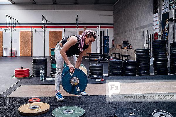 Junge Frau legt im Fitnessstudio Hantelscheibe in die Hantel