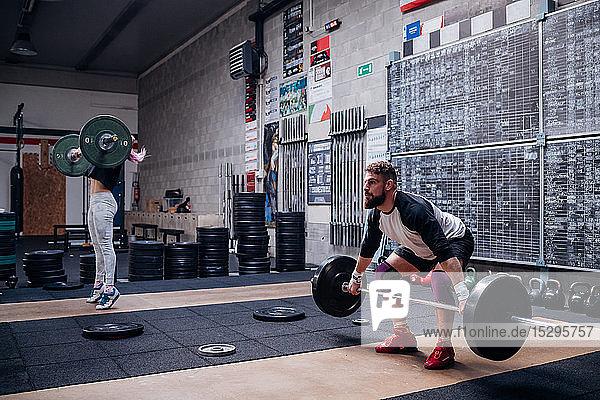 Junges Paar hebt Hantel im Fitnessstudio