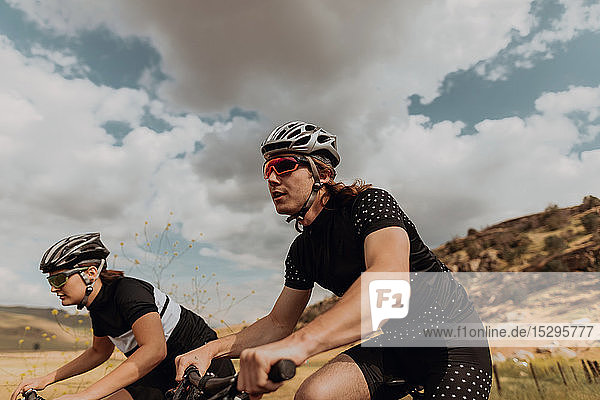 Young cycling couple cycling on rural road  side view  Exeter  California  USA