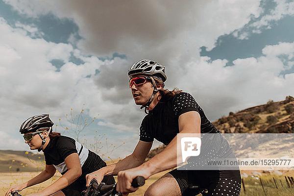 Junges Radfahrerpaar radelt auf einer Landstraße  Seitenansicht  Exeter  Kalifornien  USA
