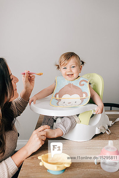 Mother feeding baby daughter in child seat  portrait