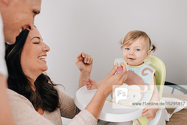 Mother and father feeding baby daughter in child seat  portrait