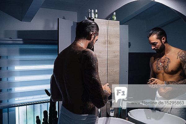 Mid adult man with tattoos getting ready at bathroom mirror