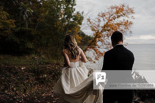 Romantischer junger Bräutigam trägt die Schleppe des Brautkleides am Seeufer  Rückansicht