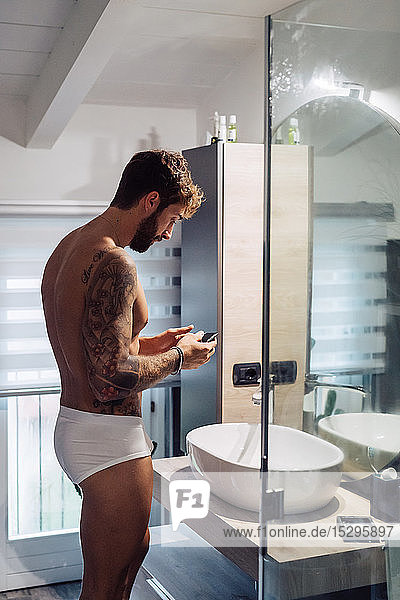 Mid adult man with tattoos looking at smartphone at bathroom mirror