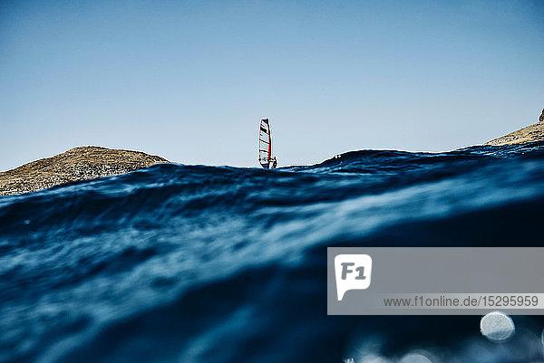 Junger Mann beim Windsurfen auf den Wellen des Ozeans  Blick auf die ferne Oberfläche  Limnos  Khios  Griechenland Junger Mann beim Windsurfen auf den Wellen des Ozeans, Blick auf die ferne Oberfläche, Limnos, Khios, Griechenland