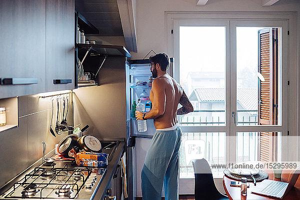 Mittelgroßer Erwachsener  der Flaschenwasser aus dem Kühlschrank entnimmt