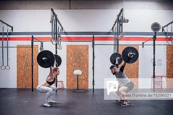 Junges Paar hockt und hebt Langhantel im Fitnessstudio