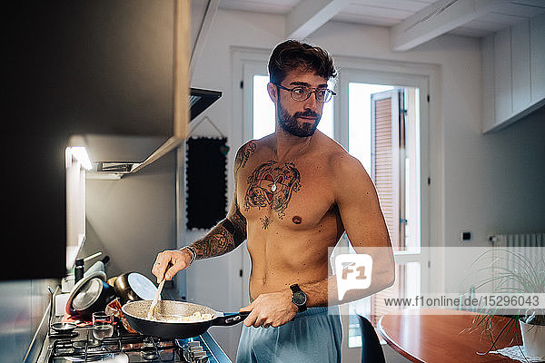 Mid adult man with tattoos cooking breakfast in frying pan