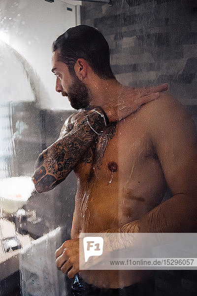 Mid adult man with tattoos taking a shower