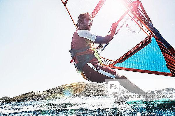 Junger Mann lehnt sich beim Windsurfen auf sonnenbeschienenen Meereswellen zurück  Limnos  Khios  Griechenland Junger Mann lehnt sich beim Windsurfen auf sonnenbeschienenen Meereswellen zurück, Limnos, Khios, Griechenland
