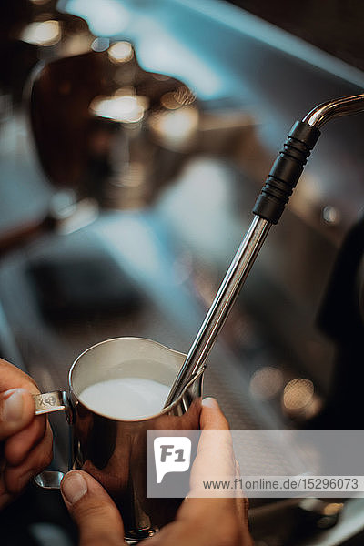 Barista heating jug of milk on coffee machine in cafe  close up of hand