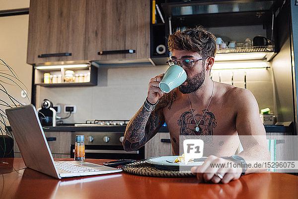 Mittelgroßer erwachsener Mann mit Tätowierungen  der Kaffee trinkt und dabei auf einen Laptop schaut