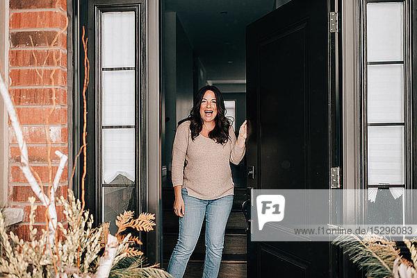 Mittlere erwachsene Frau  die die Haustür des Hauses öffnet  Porträt